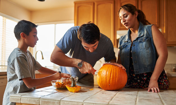 hispanic american family carving pumpkin into jack o lantern at home