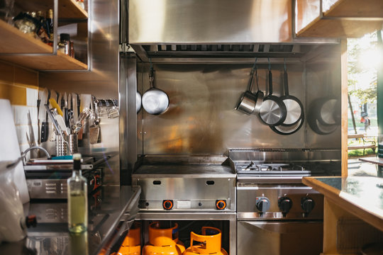 Small kitchen with stainless steel pots and pans in a rustic indoors restaurant with an open terrace at sunset. Clean and empty