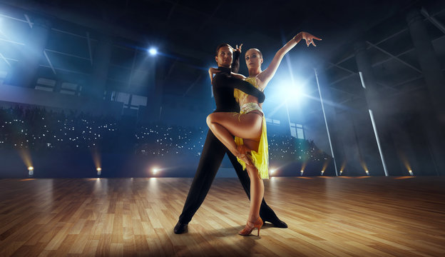 Couple dancers  perform latin dance on large professional stage. Ballroom dancing.