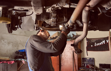 Side cropped view of auto repairman bending under bottom of car while fixing exhaust system of car. Internal garage view with tools and wrenches on background. Professional vehicle repairing