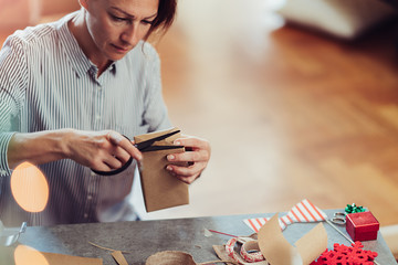 Woman wrapping Christmas presents while using scissors