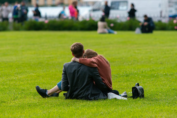 A loving couple is embracing while sitting on the grass in the park. Romance, relationship