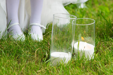 Candles in glasses on green grass. Wedding attributes. Close-up
