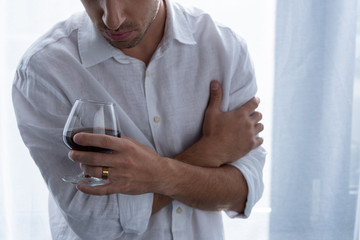 partial view of man in shirt holding glass of cognac