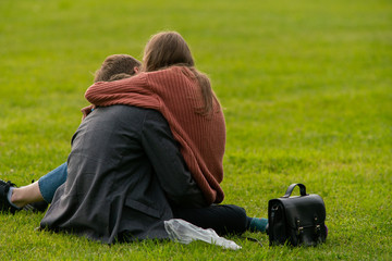Couple embracing while sitting on the grass in the park. Romance, relationship