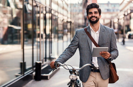 Smiling businessman using tablet on the way to office. Business, education, lifestyle concept