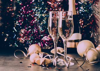 Champagne in glass goblets a bottle of Christmas toys Serpentine stars sparkling festive background. New year concept.