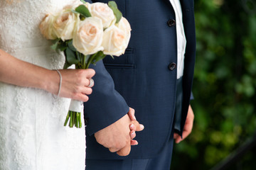 The bride and groom hold hands. A bouquet of roses in the hands of the bride. Close-up