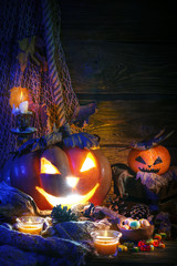 Halloween pumpkins and candy on wooden table at night.