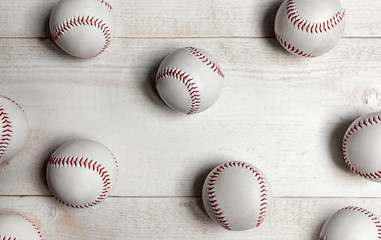 Many baseball balls on white wooden background.