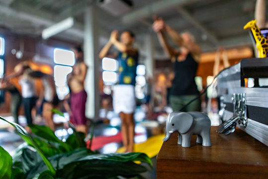 Diverse group of people in yoga class. Blurred people are seen in the background practicing 108 sun salutes with a small elephant figurine standing on a table at the front of the workshop.