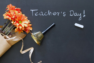 School bell and chalk on blackboard with flowers teacher day abstract background
