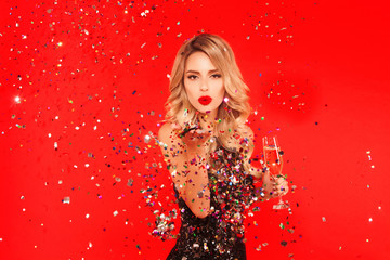 Woman with a glass of champagne celebrating New Year 2020 party. Portrait of beautiful smiling girl in shiny black dress throwing confetti on red background. Free space for text mockup