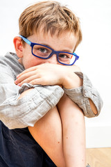 joyful child hiding giggle in knees and hands for shyness