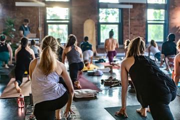 Diverse group of people in yoga class. A mixed class of men & women are seen from behind as they face the sun and stretch on exercise mats during 108 salutations to the sun. Exercises for body & mind