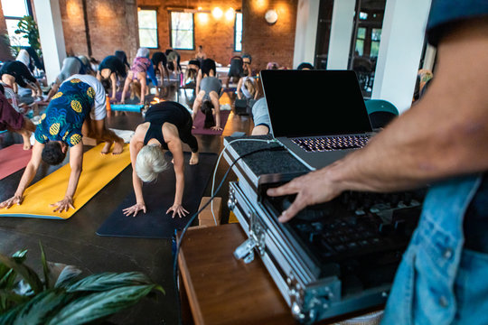 Diverse group of people in yoga class. A closeup view on the hand of a motivational guide during 108 sun salutations, operating a laptop to play relaxing music during the routine, with copy-space.