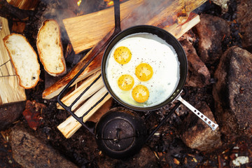 Eggs in small frying pan on bonfire. Camping in the forest.