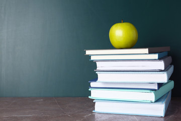 Books and apple on grey table near chalkboard, space for text. School education