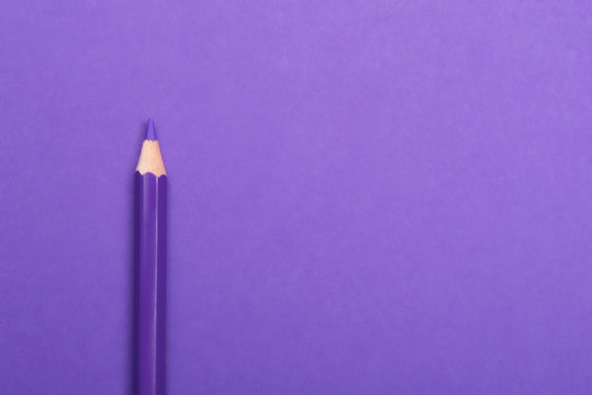 Colorful pencil on purple background, top view. Space for text