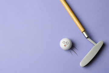 Golf ball with funny face flying away from club on lilac background - creative image. Top view