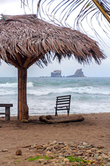 Beach parasol with a chair and bench in front of the ocean, on an overcast morning. Ayampe, Manabi, Ecuador