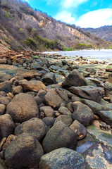 Rocks of all shapes and sizes with the beach in the background at the Los Frailes Beach National Park, Manabi, Ecuador.