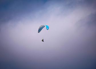 Para-glider flying in mid air over the beach, at daytime, San Pedro, Manabi, Ecuador