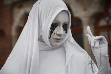 A gloomy portrait of a ghostly pale nun in white robes with black eye sockets and black smudges under them, amid gloomy Gothic architecture. Halloween, horror.