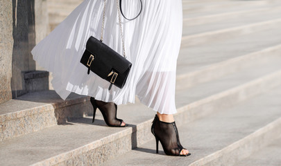 Fashionable bag close-up in female hands.Girl walks in the city outdoors. Stylish modern and feminine image, style. Girl in a white light dress with a black bag and black boots, or heeled shoes. Fotomurales