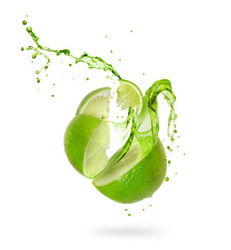 Juice splashes out of a cut lime on a white background