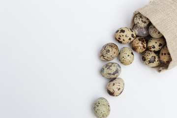 Quail eggs in fabric holder on white background. Free copy space.