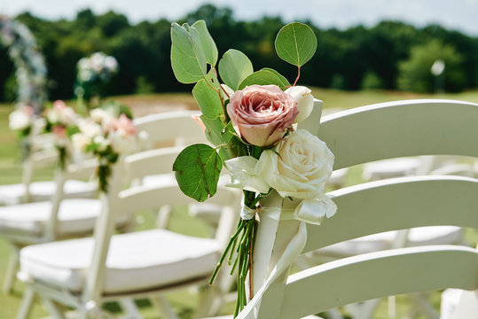 Fresh rose flowers on white wood chairs on each side of archway outdoors, copy space. Empty chairs for guests prepared for wedding ceremony on golf course