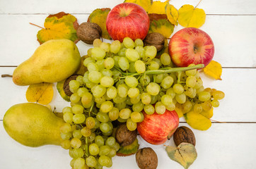 fruits on white. Apples, pears and grapes. Close-up. Beautifully laid out fruits on a  table.