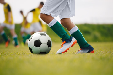 Detail soccer player kicking ball on field. Soccer players on training session. Detail soccer background. Close up of legs and feet of footballer on green grass