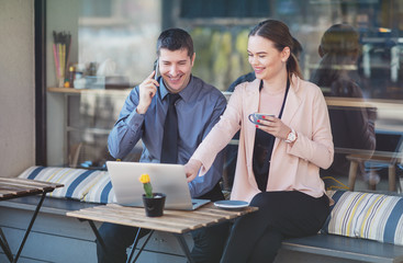 Elegant two young business people having an informal coffee meeting - Happy couple sitting on a cafe terrace flirting while using laptop and smart phone