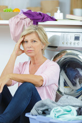 tired mature woman sat by washing machine