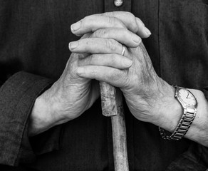 Old man's hands on his stick