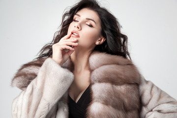 Beautiful elegant woman posing in luxury fashion fur coat over white background. Winter clother.