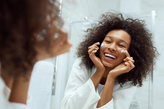 Skin care. Woman applying face cream looking in bathroom mirror
