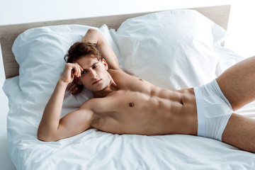 handsome and muscular young man in underwear resting on bed