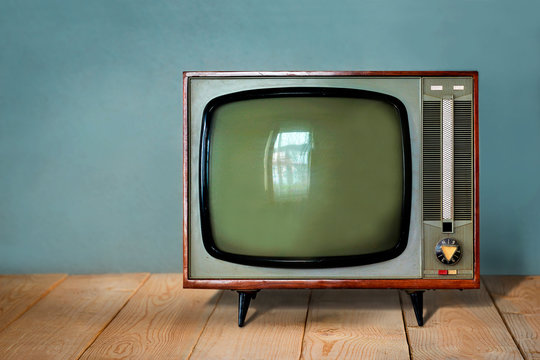 Vintage TV set on wooden table against old blue wall background