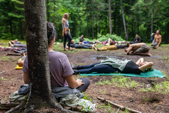 Diverse people enjoy spiritual gathering A multiethnic group of people of all ages are seen seeking enlightenment and mindfulness as they meditate in a forest clearing during a spiritual retreat.