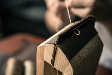 a tanner in a workshop makes a wallet from genuine leather in a special clip
