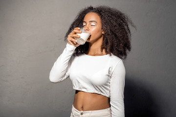 Freestyle. African girl in white outfit with bare belly standing isolated on gray drinking milk closed eyes delightful