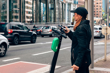 woman renting an electric scooter using a mobile phone for the payment along a city road with a traffic jam. new mobility and lifestyles concept