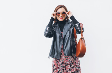 Wall Mural - Smiling middle-aged female dressed boho fashion style colorful long dress with black leather biker jacket with brown leather flap bag putting on sunglasses posing on the white wall background.