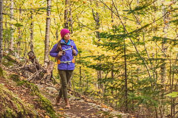Autumn hike woman walking on forest trail with yellow leaves foliage. Fall outdoor Asian girl...