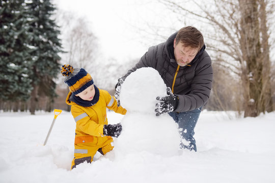 Little boy with his father building snowman in snowy park. Active outdoors leisure with children in winter.