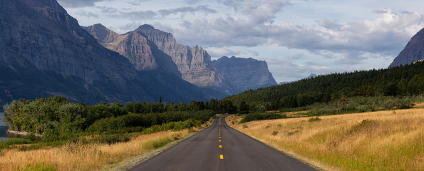 Wall Mural - Beautiful Panoramic View of Scenic Highway with American Rocky Mountain Landscape in the background during a Cloudy Summer Morning. Taken in Glacier National Park, Montana, United States.