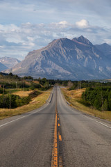 Fototapete - Beautiful View of Scenic Highway with American Rocky Mountain Landscape in the background during a Cloudy Summer Morning. Taken in St Mary, Montana, United States.